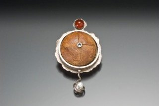 Image from Robert Danick; pin made from a leather button from a father's favorite jacket, pearl, and semi-precious stones.